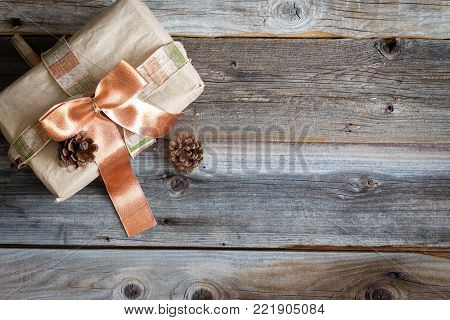 horizontal image of a Christmas gift wrapped in brown paper with a coral ribbon tied around it on a rustic wood background.
