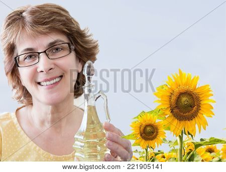 horizontal close up image of caucasian woman in a sunflower field holding a bottle of sunflower oil.