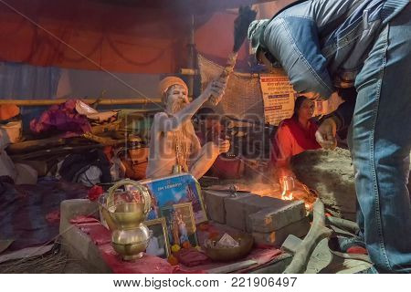 BABUGHAT, KOLKATA, WEST BENGAL / INDIA - 9TH JANUARY 2018 : Indian Hindu Sadhu , sitting with Holy ashes applied all over his body. Blessing a devotee. Shot agsint holy smoke.