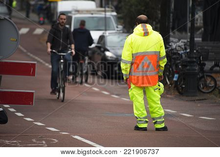 Leiden, Zuid-Holland/The Netherlands - September 29th 2017: a male traffic guard with a bright yellow light reflective suit guarding the road and stopping bikers