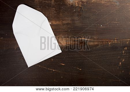 a blank empty card envelop on a wooden table background with copyspace to the left