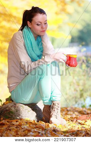 Happiness carefree and nature. Young happy woman relaxing in the autumn park enjoying hot drink coffee or tea, holding red mug with warm beverage. Yellow leaves background