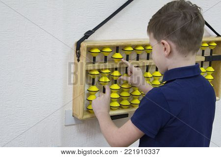 Mental arithmetic school. Boy counts with abacus in `soroban` class. Japanese abacus. Concept of back to school.copy space.