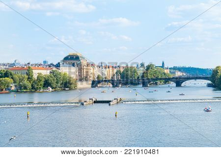 PRAGUE CZECH REPUBLIC - AUGUST 29,2017; People in small boats, sightseeing and fishing on Vltava river dissects city  and is crossed by several bridges with water management barrier across river.