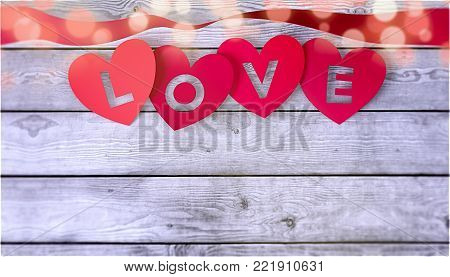 red paper hearts with text; love, and a ribbon on wooden background, valentines card (3d render)