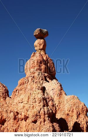 Lone hoodoo eroded by snow and ice standing against the blue sky in Bryce Canyon National Park