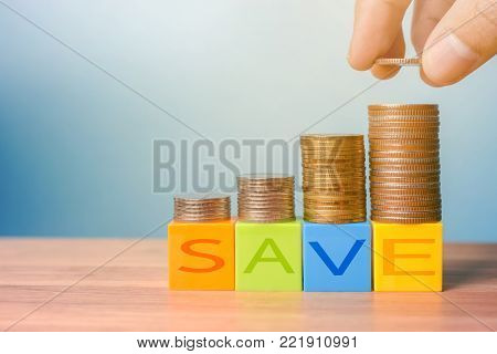 Colour blocks with SAVE and money stacks on wooden table - Saving money concept