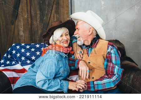 elderly couple, dressed in cowboy hats, laugh, taking each other's hands. Behind, on the couch lies the American flag, the celebration of America's Independence Day