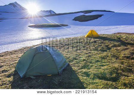 yellow tent on green field near snow hills and active volcanoes of Kamchatka at sunrise with bue sky and sun shining