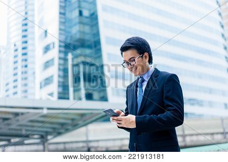 Young Asian Handsome Businessman Smilling And Using His Smartphone