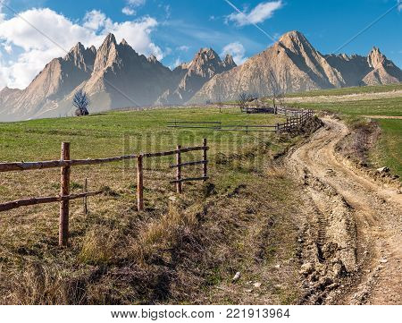road through rural fields in mountainous area. composite imagery of agricultural countryside in springtime. wooden fence along the grassy fields on hillside
