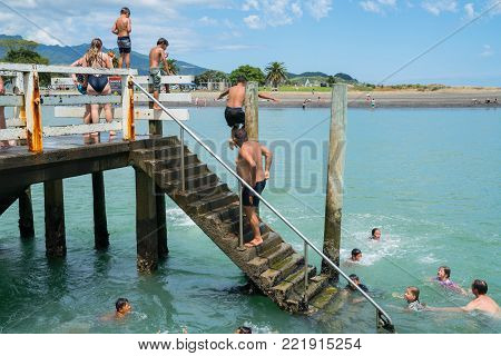 RAGLAN NEW ZEALAND - JANUARY 14, 2018; Summer fun in Raglan mostly local Maori boys jumping from the small wharf in small New Zealand town on North Island's West Coast.