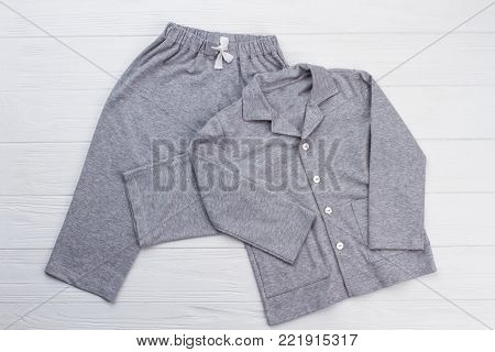 Sleepwear set on white background. Shirt and pants made of gray cotton fabric. Snugly fit and comfy pajama for boy.