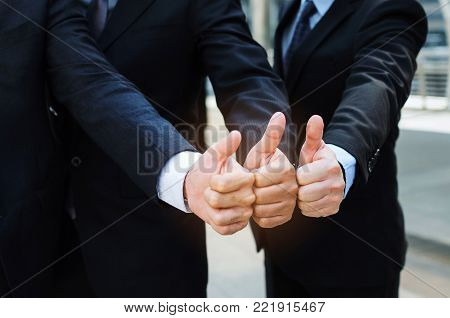 close up of hand group of handsome business people team in suit showing thumbs up as like sign together in the city, successful, support, meeting, partner, teamwork, community and connection concept