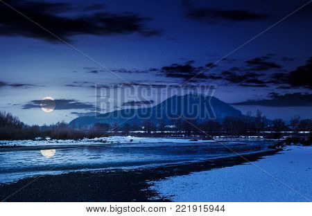 Tisza river in winter at night in full moon light. countryside area near the Khust town in Ukraine