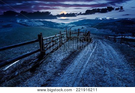 fence along the country road in rural area. lovely agricultural landscape in Carpathian mountains. grassy fields on hill in springtime at night in full moon light. Location Volovets, Ukraine