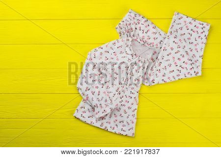 Daughter's clothes on yellow background. Adorable top with collar and ruffles and loose pants. Floral print and fashionable design.
