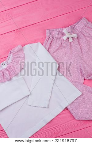 Girls' pajama on pink table. Long sleeve t-shirt with ruffle collar and pants with fine pattern. Nightwear for comfy rest.