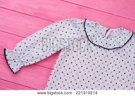 White vintage pajamas top on pink wooden background. Navy pattern of anchor and handwheel, ruffle collar and cuffs.