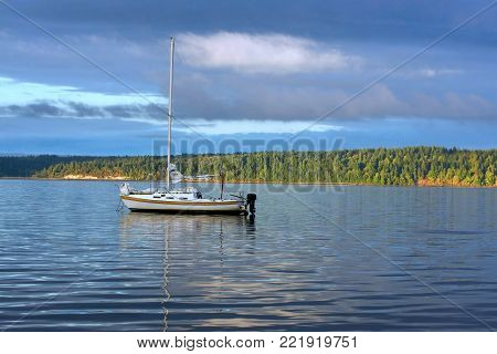 An anchored sailboat floating on calm waters.