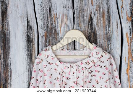 Blouse with ruffle collar and floral pattern. Girls' garment on wooden hanger over rustic background.