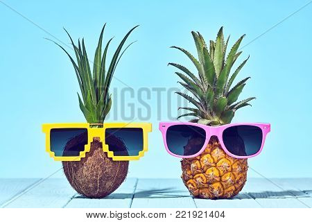 Tropical Pineapple and Coconut. Bright Summer Color. Two Hipster Fruits in Trendy Sunglasses. Fashion Style. Creative Minimal. Hot Beach Vibes. Summer party Mood