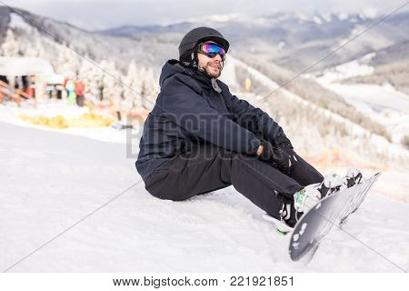 Snowboarder Sitting On A Ski Slope On Hill