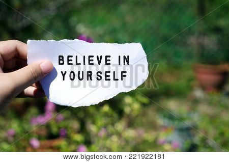 Hand holding piece of paper with inspirational quote - Believe in yourself.