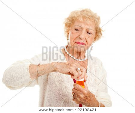 Senior woman with arthritis struggles to open a bottle of prescription medication.