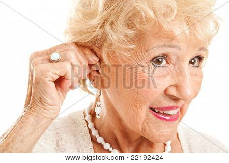Primer plano de una mujer mayor insertando un audífono en su escucha.  Se centran en el audífono.
