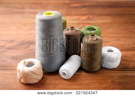 Sewing threads with clews on wooden background