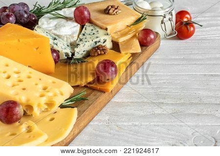 different types of cheeses on wooden cutting board. Camembert cheese, cheddar, hard cheese slices, soft cheese, walnuts, grapes, tomatoes and rosemary. close up