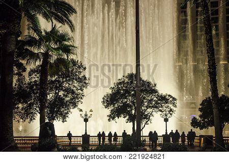 LAS VEGAS, NEVADA, USA- NOVEMBER 15, 2017: Night scene with silhouettes of people admiring the Bellagio fountains spectacle at Las Vegas, Nevada
