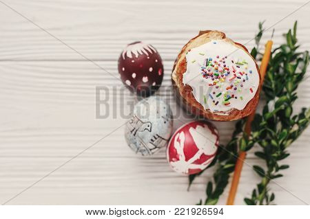 stylish easter bread and painted eggs on rustic wooden background top view with candle and greenery. happy easter flat lay, greeting card. space for text