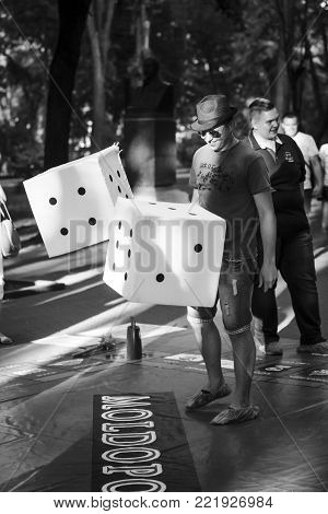 6 june 2015 an unidentified guy plays in a busines game on the street with big cubes,black and white photo, Chisinau, Moldova