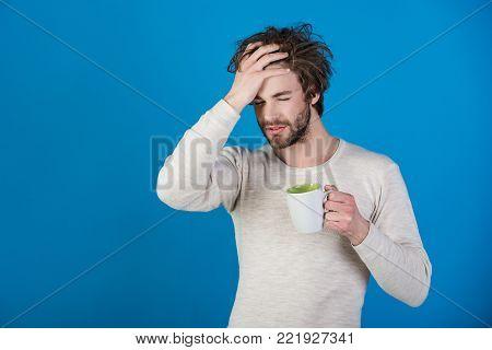 Sleepy Guy With Tea Cup Has Headache On Blue Background.