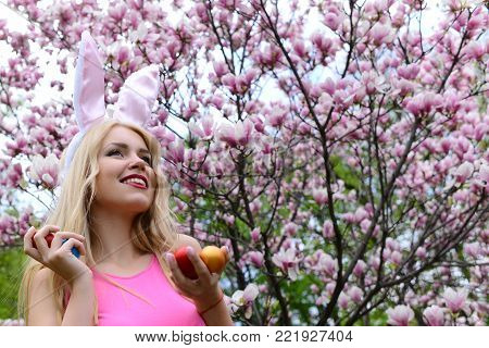 woman or pretty girl smiling with colorful eggs with pink, bunny ears on long, blond hair in rosy top in blossoming magnolia garden on floral environment. Spring. Easter, holidays, celebration