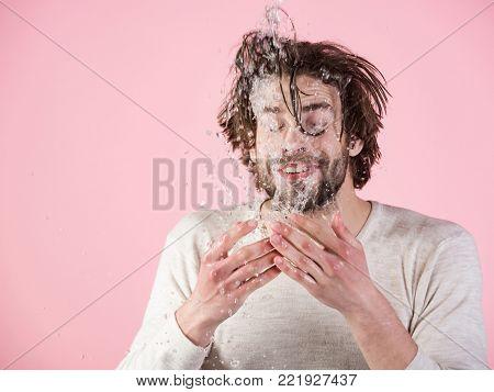 Refreshment and healthcare. Hygiene, guy wash happy face. Man with disheveled wet hair washing face. Man splash water at face on pink background. Morning washing, wake up, everyday life.