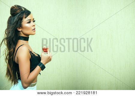 Girl holding glass of wine on beige wall. Woman with long brunette hair in black lace bustier. Cocktail party or holiday celebration. Drinking alcohol concept. Bad habit and addiction, copy space