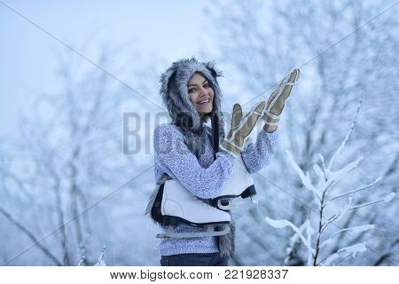 Woman skater with figure skates in fur hat, mittens, sweater smile in snowy forest outdoor. Winter fashion, style. Vacation, holidays, hobby, lifestyle. Ice skating, sport, activity, health concept.