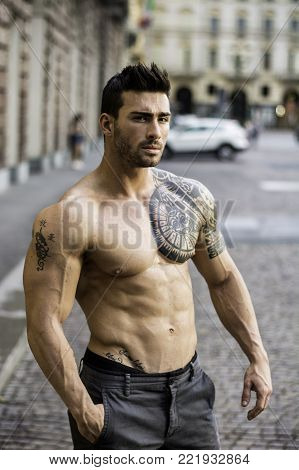 Handsome muscular shirtless man with tattoo posing in European city center, Turin, Italy