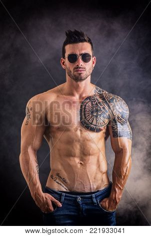 Handsome shirtless muscular man with jeans, standing and wearing sunglasses, on dark smoky background in studio shot