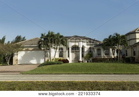 Typical Southwest Florida concrete block and stucco home in the countryside with palm trees, tropical plants and flowers, grass lawn and pine trees. Florida.