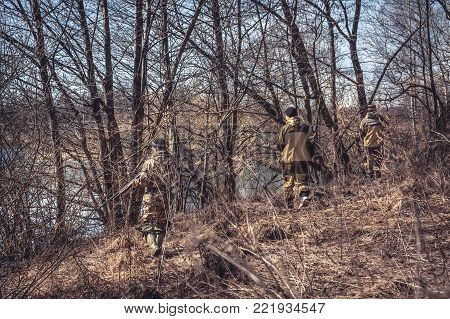 Group of  hunters in camouflage stealing in spring forest during hunting season