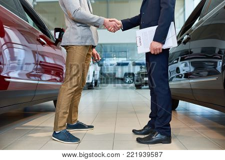 Low section side view of  handsome client shaking hands with sales manager in car showroom, after buying brand new luxury car