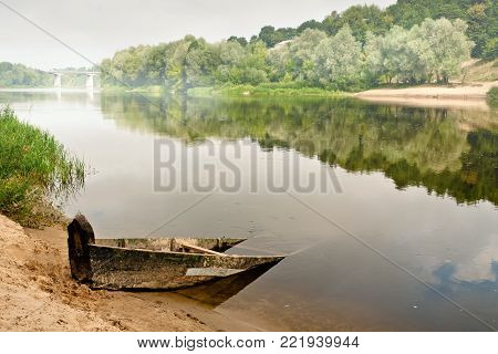 an old wooden boat half submerged in the water on a misty summer morning overlooking the bridge