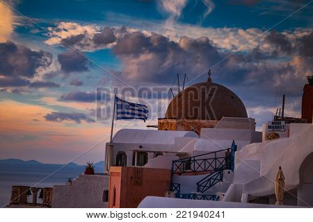 Oia sunset view with Greece flag and traditional houses, Cyclades, Greece.