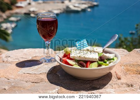 A glass of red wine and bowl of greek salad with greek flag on a stone terrace by the sea view, summer greek holidays concept. Horizontal. Daylight.