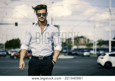 One handsome elegant young man in urban setting in European city, standing