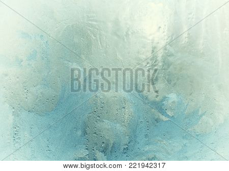 Fantastic fairy-like frost pattern on the window glass (as an abstract winter background), retro toned